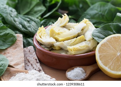 Artichoke hearts, spinach, lemon and other ingredients for vegan dip.