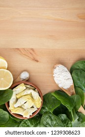 Artichoke hearts, spinach, lemon and other ingredients for vegan dip flat lay with copy space