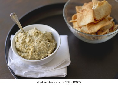 Artichoke hummus with pita chips on a plate.