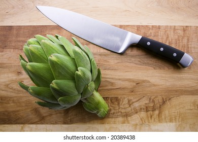 Artichoke and knife on Cutting board
