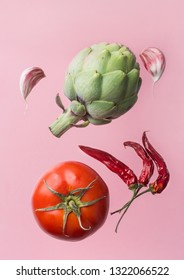 Artichoke ripe juicy tomato hot chili peppers garlic cloves floating levitating on pink background. Creative food art poster. Mediterranean cuisine healthy diet superfoods concept