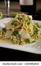 Artichoke Spaghetti Alla Chitarra served with Parmesan Cheese slices and basil on a white plate