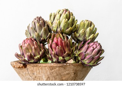 artichokes inside a wooden bowl with a white wall background