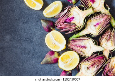 Artichokes on dark background and lemons copy space flat lay.
