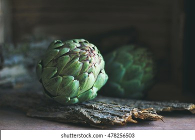Artichokes with wooden background in dark food photography style