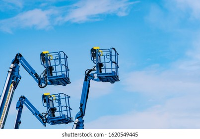 Articulated boom lift. Aerial platform lift. Telescopic boom lift against blue sky. Mobile construction crane for rent and sale. Maintenance and repair hydraulic boom lift service. Crane dealership.