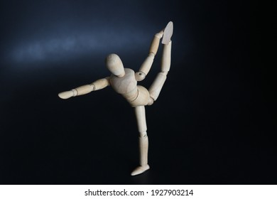Articulated doll of light wood in a representative ballet position with dark background.
