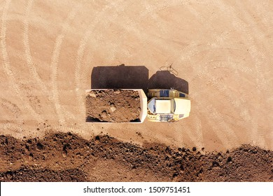 Articulated hauler Truck loaded with Soil at an industrial development site, Topdown aerial image.