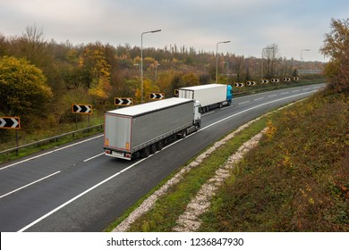 Articulated lorries in motion on the road.