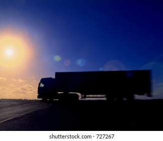 Articulated lorry heading into the sunset. deliberate zoom blur and flare.
