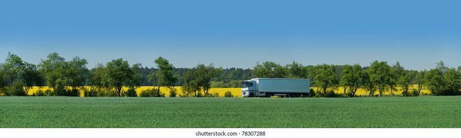 Articulated vehicle runs on an alley between adjacent fields in Brandenburg, Germany