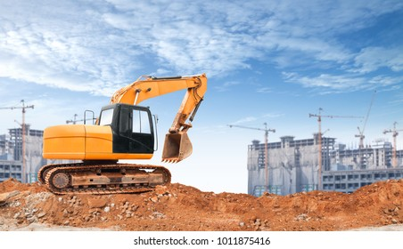 An articulated wheel crawler loader or dozer on mound with the industrial building construction site and blue sky background concept