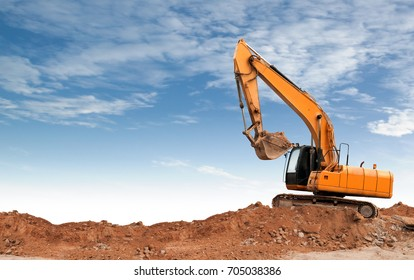 An articulated wheel crawler loader or dozer on mound in the industrial building construction site