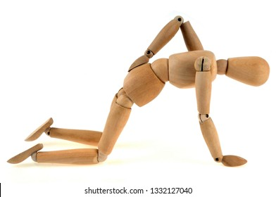 Articulated wooden dummy suffering from sciatica on a white background