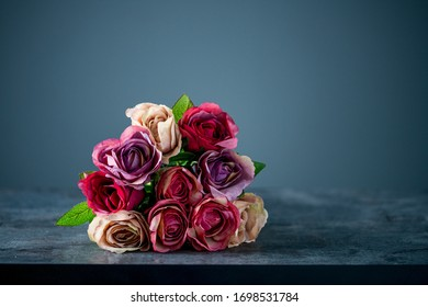 Artificial antique roses on stony background.