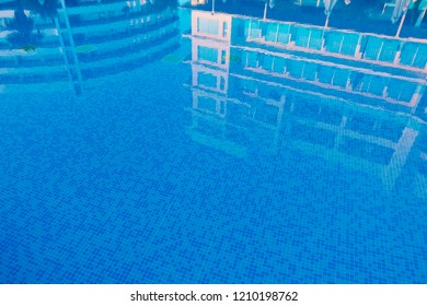 Artificial background: reflection of hotel buildings in a swimming pool water surface. Summer getaway.