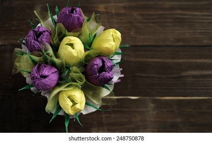 Artificial bouquet of tulips in a jug on a wooden table. Top view.