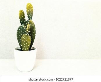 Artificial cactus in white ceramic pot. Faux plant. Modern home decor.