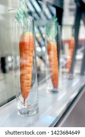 Artificial carrots in long transparent glasses on the show-case. Concept picture.