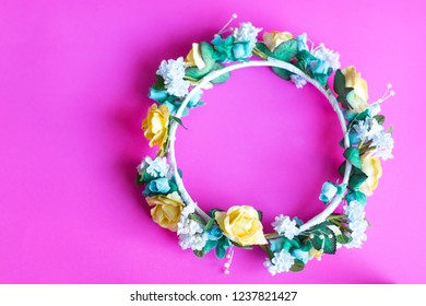 Artificial chaplet (wreath of flowers) of yellow roses and blue flower on pink background with copy space.