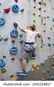 Artificial climbing facility and Caucasian boy with safety line on walls