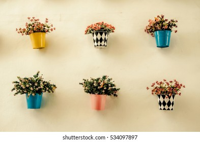 Artificial colorful flower pots hang onto the wall. Processed with vintage style,can be used for background