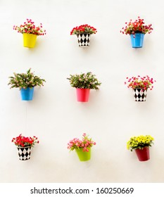 Artificial colorful flowers pots hang onto the wall