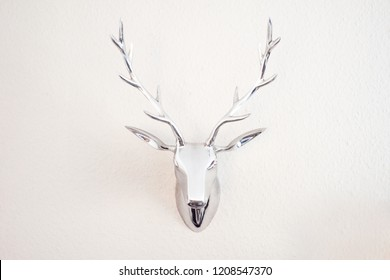 An artificial deer head is hanging on the wall. Polygonal deer head. The subject of art on the wall. Volumetric model. Metal head