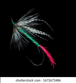 Artificial fishing fly isolated on a black background.