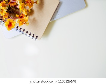 artificial flower and brown book on computer laptop lay on white table, with free copy space