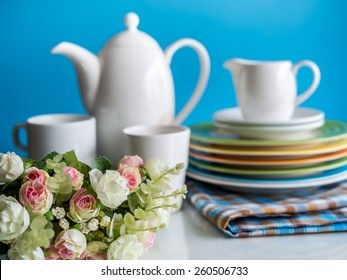 Artificial flower with colorful dishware utensil on table top blurred background