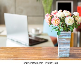 Artificial flower vase on table top over blurred image of  modern workplace background