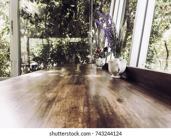 Artificial Flower Vase on a wooden table in a cafe, beautifully decorated in a garden setting.