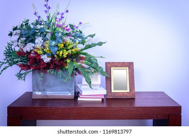 Artificial flower vase, photo frame & books decoration on wooden table in modern Living room / Home improvement design concept