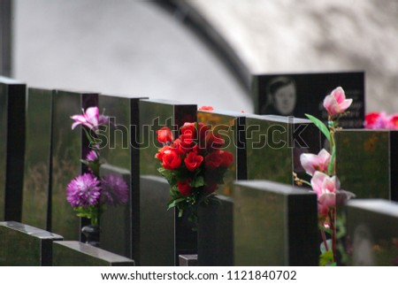 Artificial flowers among black obelisks in the cemetery
