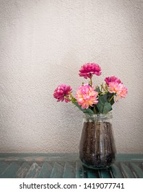 artificial flowers bouquet in transparent glass vase on rough wall background