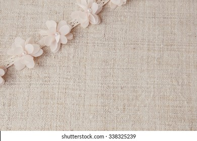 Artificial flowers and lace on linen, copy space background, selective focus, vintage tone
