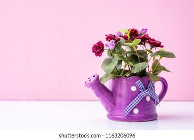 Artificial flowers in pink watering