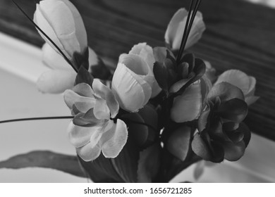 Artificial flowers sitting on a vase indoors in black and white