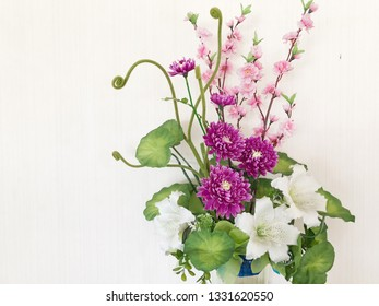 Artificial flowers in vase on white background