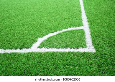 Artificial grass of football field with white stripe, Soccer corner line detail, Green astro turf for texture background, Perspective