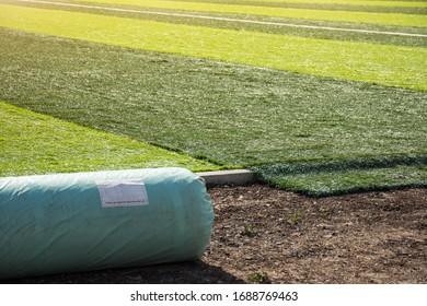 Pelouse artificielle sur le sol avec gazon artificiel en arrière-plan