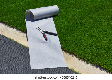 Artificial grass turf installation in garden with tools and joint roll