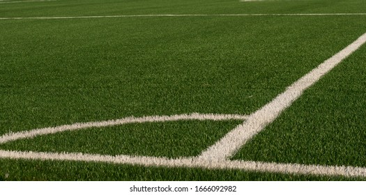 Artificial green grass and white border lines. Artificial turf for soccer field. Football field in an outdoor stadium. Selective focus.