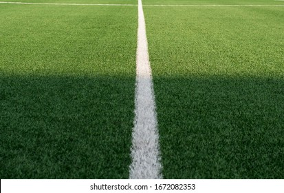 Artificial green grass and white border lines. Artificial turf for soccer field. Football field in an outdoor stadium. White lines on the road. Selective focus.