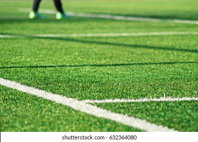 Artificial green grass  with white stripe of soccer field. White line on green grass a field of play. Fake Grass used on sports fields for soccer and football. Closed-up of artificial grass background