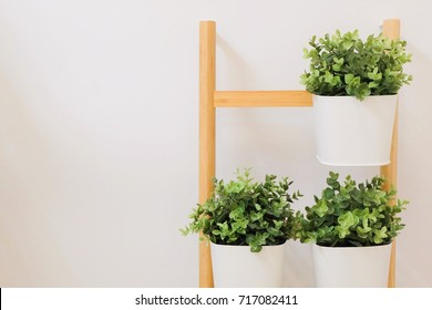 Artificial Green Plants in A White Metal Flower Pots Stand on The Wooden Shelves, for Home and Office Decoration without The Care.