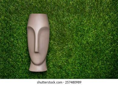 Artificial head lying on green grass