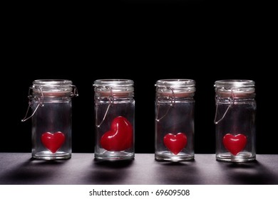 Artificial hearts in glass cans. Studio shot, isolated on black.