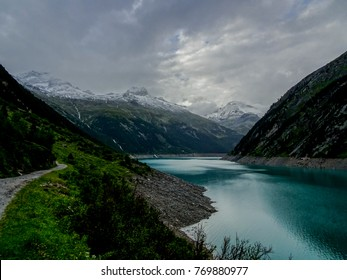 Artificial high alpine mountain lake in the austrian alp region tyrol in the valley zillertal on a very cloudy day with high mountains in the background panorama covered with snow and ice